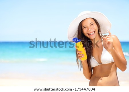 Sunscreen beach woman in bikini applying sun block solar cream for UV protection. Girl smiling to camera, wearing white sun hat, happy on vacation travel holiday. Hawaii, USA - stock photo