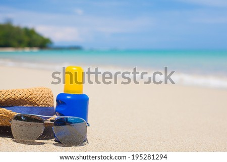Sunscreen, hat and sunglasses on tropical beach - stock photo