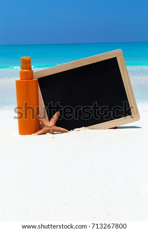 Sunscreen lotion in orange tube with chalk board decorated star fish on sandy beach. Skin care concept card with sea background