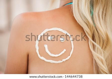 Sunscreen lotion over tan woman skin made as smiling face - stock photo