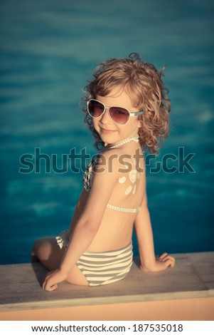 Sunscreen lotion sun drawing on children back. Child having fun in swimming pool. Summer vacation concept. Healthy lifestyle - stock photo
