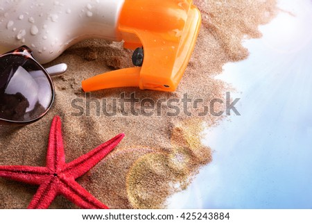 Sunscreen spray and sunglasses on sand in blue glass table with sun shine. Horizontal composition. Elevated view - stock photo