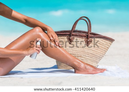Sunscreen suntan lotion spray skincare product closeup of woman putting tanning oil on her legs. Hand holding sunblock or mosquito repellent bottle spraying on body sunbathing at beach summer vacation - stock photo