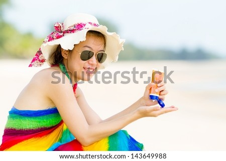 Sunscreen woman. Girl sun block on beach holding - stock photo