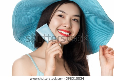 Sunscreen woman wearing blue straw hat holding suntan cream tube isolated on white background. - stock photo