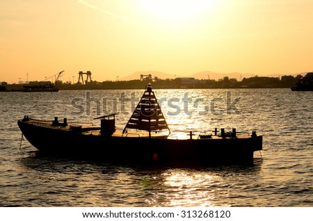 Sunset, a boat on the river n a golden atmosphere - stock photo