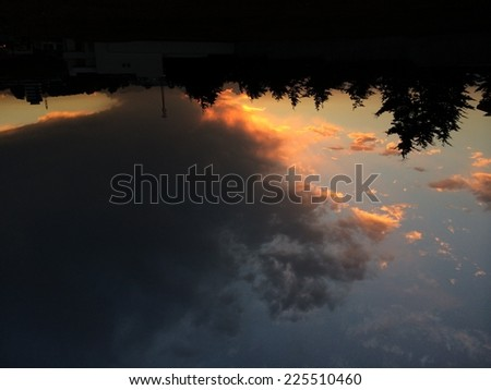 Sunset above a building with dark clouds in the sky. - stock photo