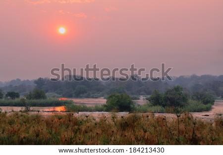 Sunset above Okavango river from campsite near Popa falls, North Namibia - stock photo