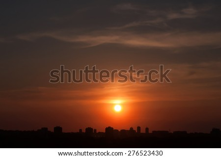 Sunset above the city with silhouettes of buildings - stock photo