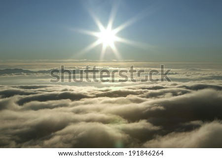 Sunset above the clouds rolling in the valley - stock photo