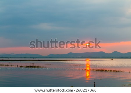 sunset above the  river with mountain far away - stock photo