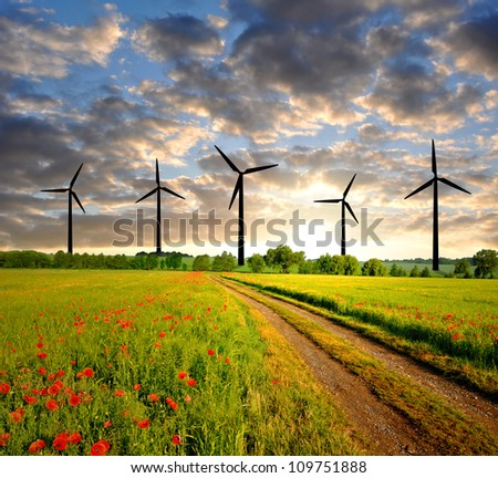 sunset above the spring landscape with wind turbines - stock photo