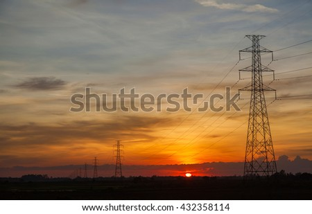 Sunset against high electric voltage pole landscape - stock photo