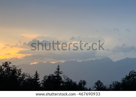 Sunset against mountains in clouds