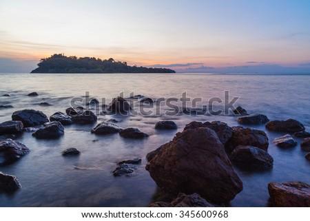 Sunset againt rock on sea beach - stock photo