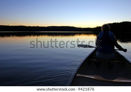 Sunset and canoe trip in calm lake in Algonquin Park