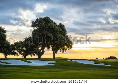 sunset and golf course with flag - stock photo