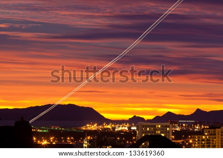 Sunset and light trail of starting airplane over Manukau  southern suburb of Auckland  New Zealand - stock photo