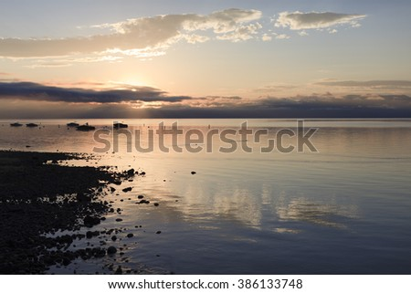 Sunset and pink clouds over lake surface of Lake Tahoe - stock photo