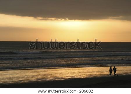 Sunset and runners at Kuta Beach Bali - stock photo