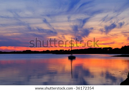 Sunset and sailboat in Martha's Vineyard, Massachusetts. Dramatic sky with vivid orange and blue cloudscape reflected on the water - stock photo