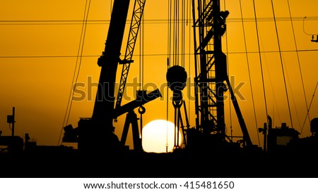 Sunset and silhouette of crude oil pump, drilling rig  and a crane working together in oilfield