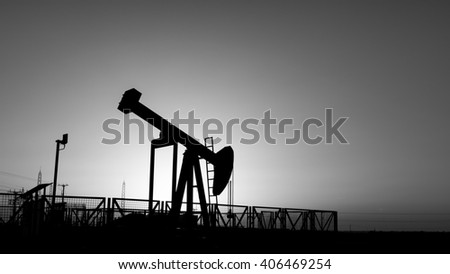 Sunset and silhouette of crude oil pump in oilfield - black and white