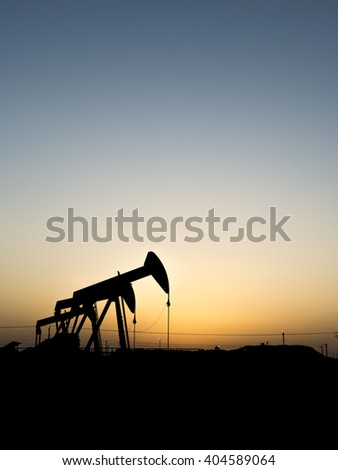 Sunset and silhouette of crude oil pump units in oilfield.