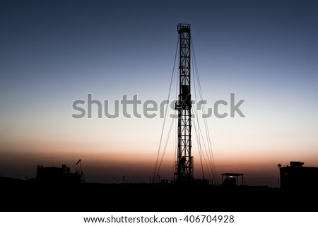 Sunset and silhouette of drilling rig in oilfield  - stock photo