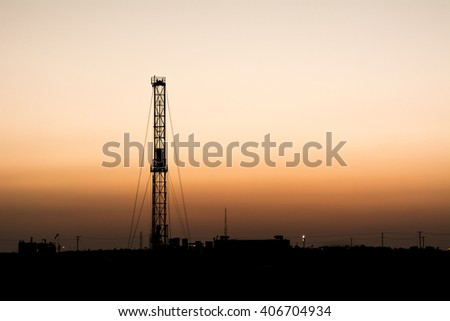 Sunset and silhouette of drilling rig in oilfield