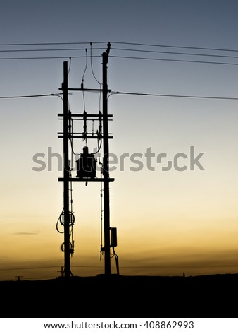 Sunset and Silhouette of electrical transformer in the oilfield