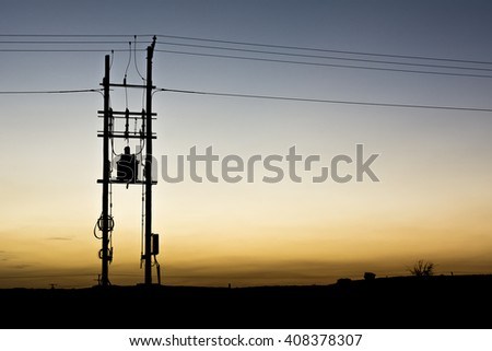 Sunset and silhouette of electrical transformer on pole- oilfield