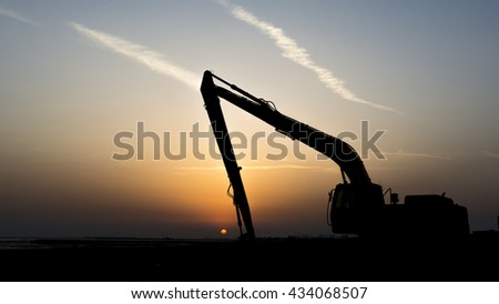 Sunset and silhouette of excavator on the reclamation land.