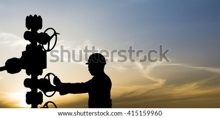 Sunset and silhouette of oilfield worker controlling valves on wellhead  in oilfield