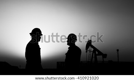 Sunset and silhouette of oilfield worker in the oilfield - Blur crude oil pump background - black and white - stock photo