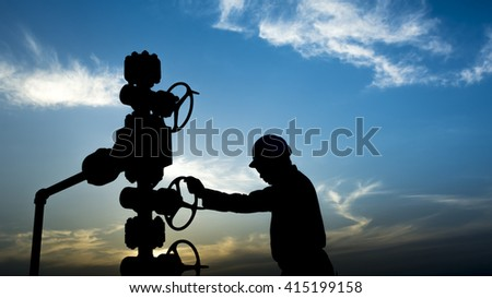 Sunset and silhouette of oilfield worker monitoring wellhead controls in oilfield  - stock photo