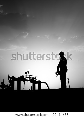 Sunset and silhouette of oilfield worker monitoring wellhead manifold in oilfield - black and white