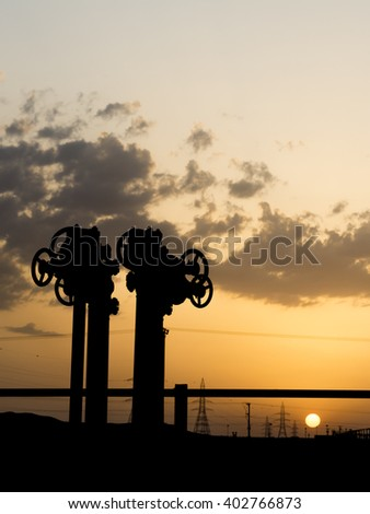 Sunset and silhouette of pipeline valves
