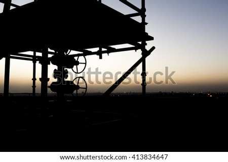 Sunset and silhouette of wellhead surrounded by scaffold pipes in oilfield