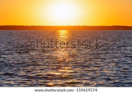 Sunset and sun track on summer lake surface.