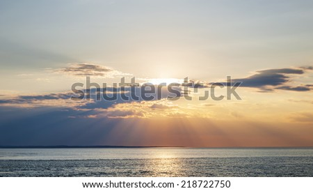 Sunset and sunbeams with dramatic sky over Atlantic Ocean in Prince Edward Island, Canada - stock photo