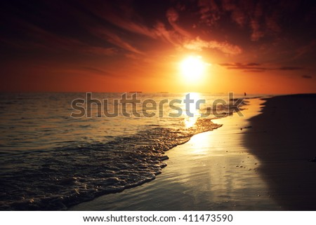 Sunset and surf on tropical beach - stock photo