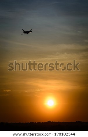 Sunset and the taking off aircraft - stock photo