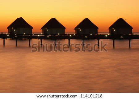 Sunset and water bungalows, abstract vacation background - stock photo