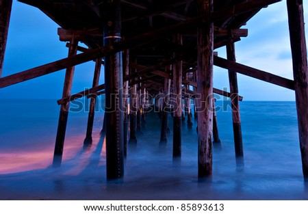 Sunset as seen from shore, looking out directly under Balboa Pier, Newport Beach, California. - stock photo