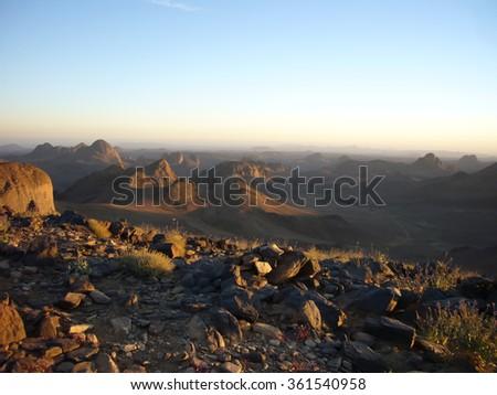 Sunset at Assekrem in the middle of black mountains of Hoggar desert, Algeria - stock photo