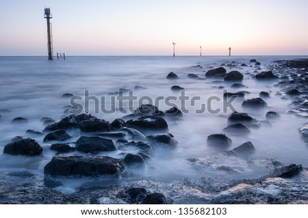 Sunset at beach with boulders and masts in the water