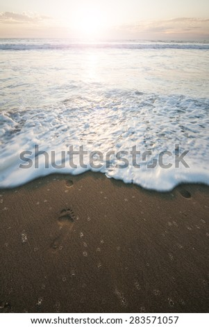 Sunset at beach with water waves foam and footprint