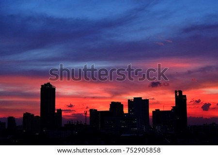 Sunset at city of Bangkok with building silhouette.