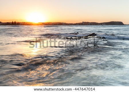Sunset at Currumbin Rock Gold Coast with ocean tide flowing across the rock
